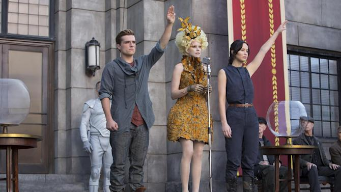 """This image released by Lionsgate shows Josh Hutcherson as Peeta Mellark, from left, Elizabeth Banks as Effie Trinket and Jennifer Lawrence as Katniss Everdeen in a scene from """"The Hunger Games: Catching Fire."""" The movie opens in theaters Friday, Nov. 22, 2013, in what's expected to be one of the year's biggest box-office debuts. (AP Photo/Lionsgate, Murray Close)"""