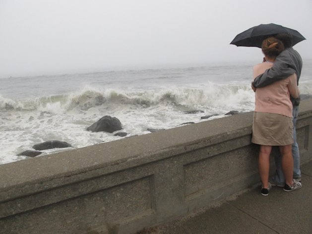 In this Aug. 27, 2011 photo, Sarah Pease-Kerr and Chris Barrett of South Kingstown, R.I., watch waves from Hurricane Irene crash onto the shore on in Narragansett, R.I. (AP Photo/David Klepper)