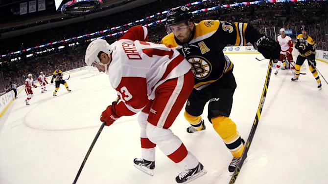 In this photo taken with a fisheye lens, Detroit Red Wings' Pavel Datsyuk (13) tries to keep the puck from Boston Bruins' Patrice Bergeron during the first period of Game 1 of a first-round NHL playoff hockey series in Boston on Friday, April 18, 2014