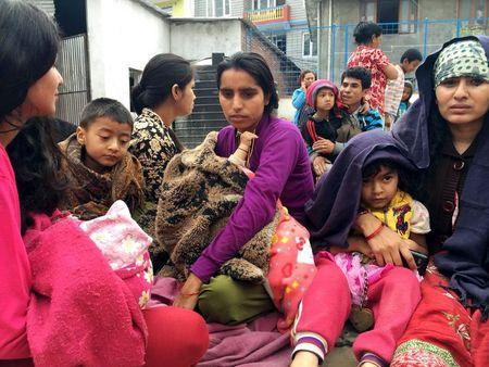 People wait at a school after a 7.7 magnitude earthquake struck, in Kathmandu, Nepal