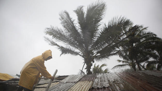 "Gumercindo Gomes, 48, tries to fix the roof of a bar at the Playa Azul, or ""Blue beach"" as Tropical Storm Arlene arrives in Tuxpan, Mexico, Thursday, June 30, 2011. Tropical Storm Arlene struck land near Cabo Rojo, a cape just off the mainland between the cities of Tampico and Tuxpan. It had maximum sustained winds of 65 mph (100 kph) and was moving inland at 8 mph (13 kph), according to the U.S. National Hurricane Center in Miami. (AP Photo/Alexandre Meneghini)"