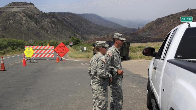 National Guard soldiers stop a motorist at a road block along Highway 14 north of Laporte, Colo., on Sunday, June 17, 2012, as the High Park Fire continues to burn in Fort Collins, Colo. Crews are facing powerful winds as they battle the blaze that has scorched about 86 square miles of mountainous forest land and destroyed at least 181 homes, the most in state history. (AP Photo/David Zalubowski)