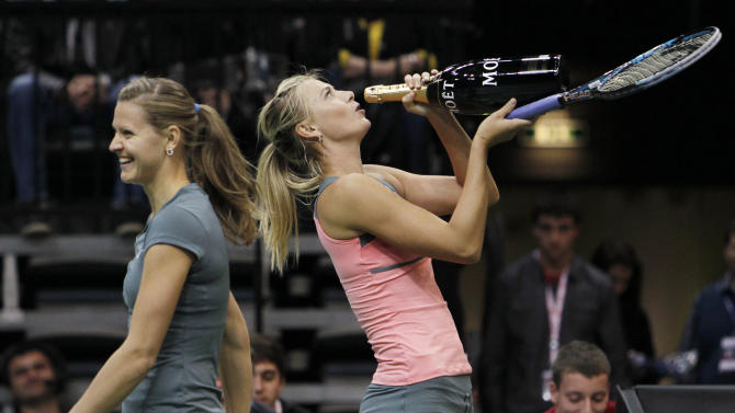 Russia's Sharapova pretends to drink out of a bottle of a sparkling wine next to Czech Republic's Safarova during an exhibition tennis match in Prague