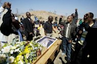 <p>A group of men sing and raise their fists in salute at the coffin of Mpuzeni Ngxande, one of 34 striking miners killed by police on August 16 near the Lonmin mine in Marikana. A local media report Wednesday raised further questions about whether police who opened fire on the miners were acting in self-defence, as they have claimed.</p>