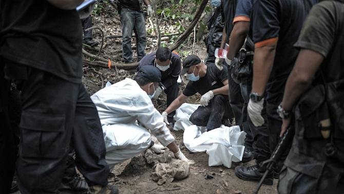 A forensics team handles exhumed human remains in a jungle at Bukit Wang Burma in Perlis, Malaysia, which borders Thailand on May 26, 2015
