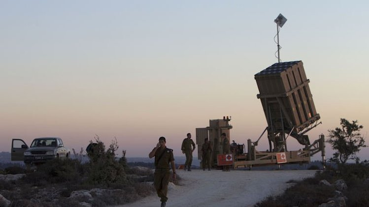 """Israeli soldiers stand near an """"Iron Dome"""" battery, near Jerusalem on September 8, 2013"""