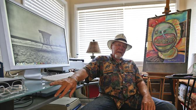 In this July 16, 2014 photo, artist Michael Gross, who is battling cancer, sits in his studio between one of his paintings and one of his photos on his computer screen in Oceanside, Calif. Gross has decided to use his art and the work of other artist to raise money in his fight against cancer. (AP Photo/Lenny Ignelzi)