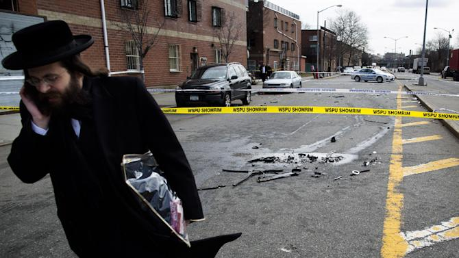 A man walks past debris from a fatal accident that claimed the lives of two expectant parents on their way to the hospital early, Sunday, March 3, 2013, in the Brooklyn borough of New York. A driver struck the car the couple were riding in early Sunday morning, killing both parents while their baby, who was born prematurely, survived and is in critical condition. (AP Photo/John Minchillo)