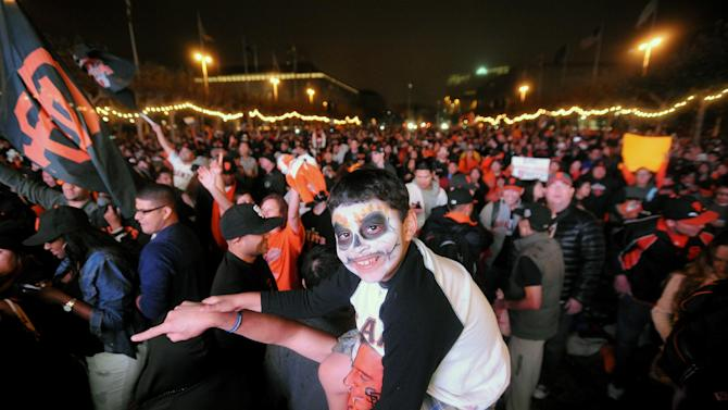 San Francisco Giants fans celebrate outside San Francisco's City Hall while watching a broadcast of the Giants facing the Detroit Tigers in Game 4 of baseball's World Series on Sunday, Oct. 28, 2012. The Giants won the game to sweep the series. (AP Photo/Noah Berger)