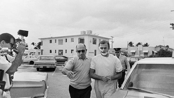 """FILE - In this Jan. 28, 1968 file photo, Jack """"Murph the Surf"""" is escored to the Miami Beach Police Station by detectives in Miami Beach, Fla., after he was arrested with three other men for armed robbery. Murphy, the famed jewel thief and surfer known as """"Murph the Surf,"""" has spent the last quarter-century going into prisons and telling inmates that they could still turn their lives around.  Now 75, he asked the state of Florida to restore his civil rights despite the fact he spent nearly 20 years in prison for murder. The answer: No. (AP Photo, File)"""