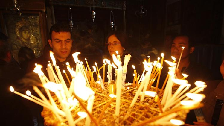 Christian worshippers light candles following Christmas day Mass at the Church of the Nativity, traditionally believed by Christians to be the birthplace of Jesus Christ, in the West Bank town of Bethlehem, Sunday, Dec. 25,2011. Hundreds of Christian faithful, defying lashing rains and wind, celebrated Christmas Mass at Jesus' traditional birthplace on Sunday, spirits high despite the gloomy weather.(AP Photo/Majdi Mohammed)