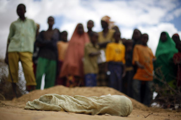 FILE - In this Saturday Aug. 6, 2011 file photo, the shrouded body of 12-month-old Liin Muhumed Surow, who died of malnutrition 25 days after reaching the camp according to her father Mumumed, lies be