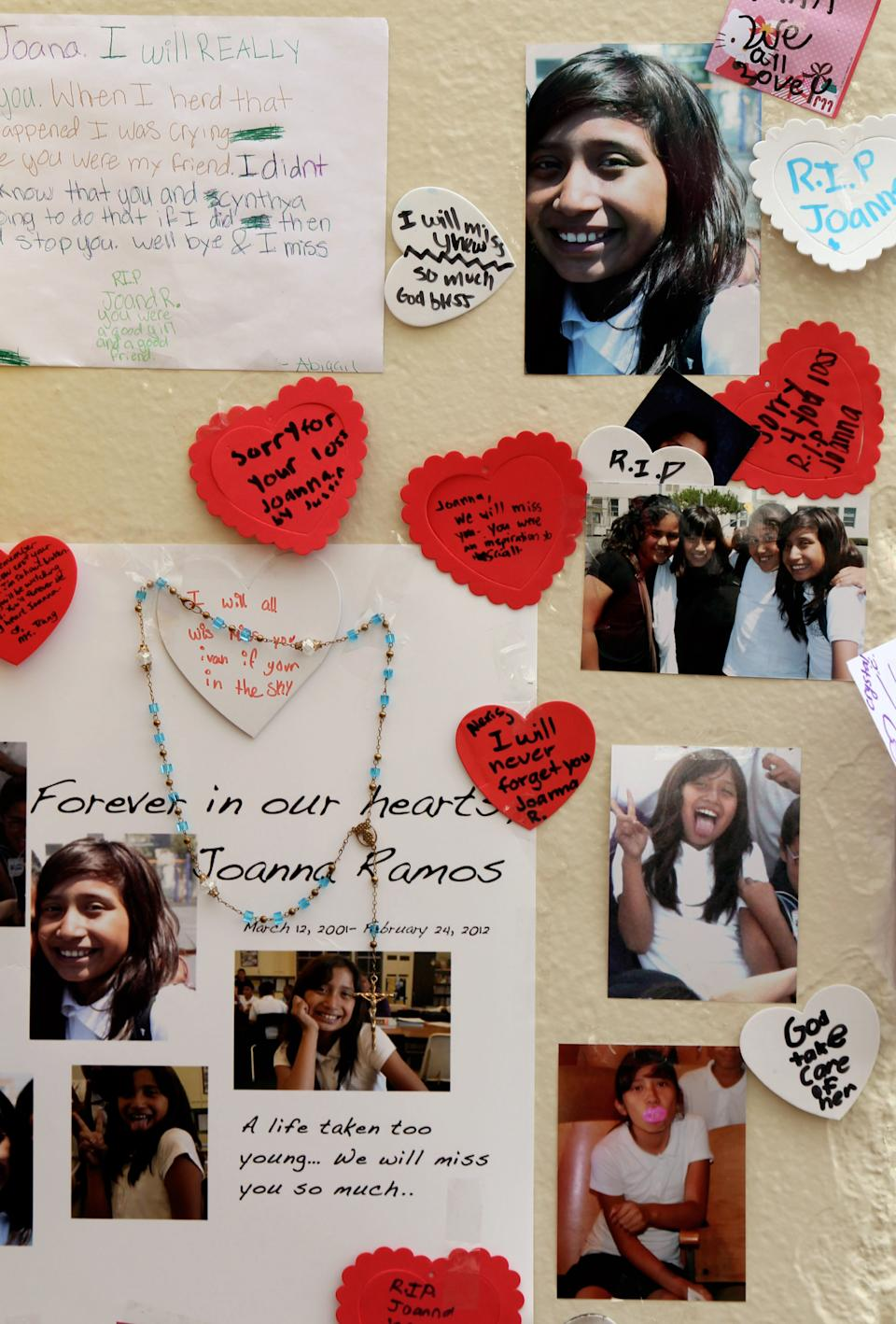 Photos with notes are left at a memorial outside Willard Elementary School for Joanna Ramos, 10, in Long Beach, Calif. on Monday Feb. 27,2012.  The Los Angeles County coroner's office has ruled that the death Ramos a Southern California schoolgirl after a fight was a homicide.  (AP Photo/Nick Ut)