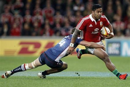 British and Irish Lions player Tuilagi is tackled by English from the Melbourne Rebels during their rugby game in Melbourne