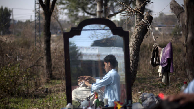 Roadside barber Adnan Khan shaves his customer in the suburbs of Islamabad, Pakistan on Tuesday, Feb. 12, 2013. Khan earns about Rs. 600 (US$6) a day to feed his family living in slum. (AP Photo/B.K. Bangash)
