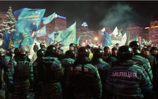 Riot police stand in front of tents set up by pro-European integration protesters at Independence Square in Kiev