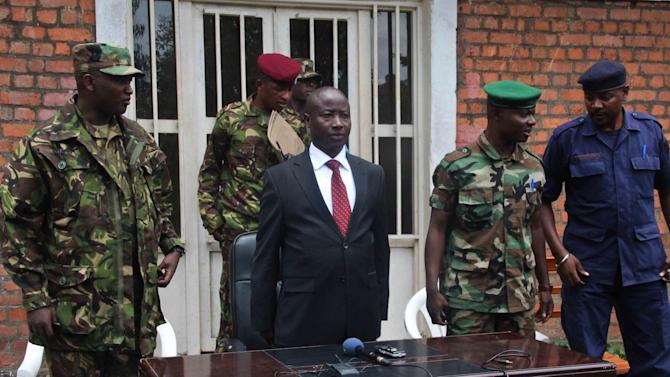 In this photo taken Monday, March 4, 2013, former M23 President Jean-Marie Runiga, center, is accompanied by general Baudoin Ngaruye, left, as he holds a press conference in Kibumba, eastern Congo, following a split within the M23 rebel group. Col. Vianney Kazarama, leader of the rival faction, said Saturday, March 16, that his faction has regained control of all the M23 held territory in eastern Congo, and that Runiga has been arrested by Rwandan authorities after fleeing across the border. (AP Photo/Melanie Gouby)