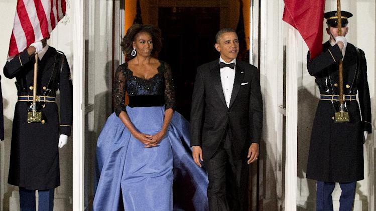 FILE - This Feb. 11, 2014 file photo shows President Barack Obama and first lady Michelle Obama arrive at the North Portico of the White House in Washington to greet French President François Hollande, who is arriving for a State Dinner. (AP Photo/ Evan Vucci, File)