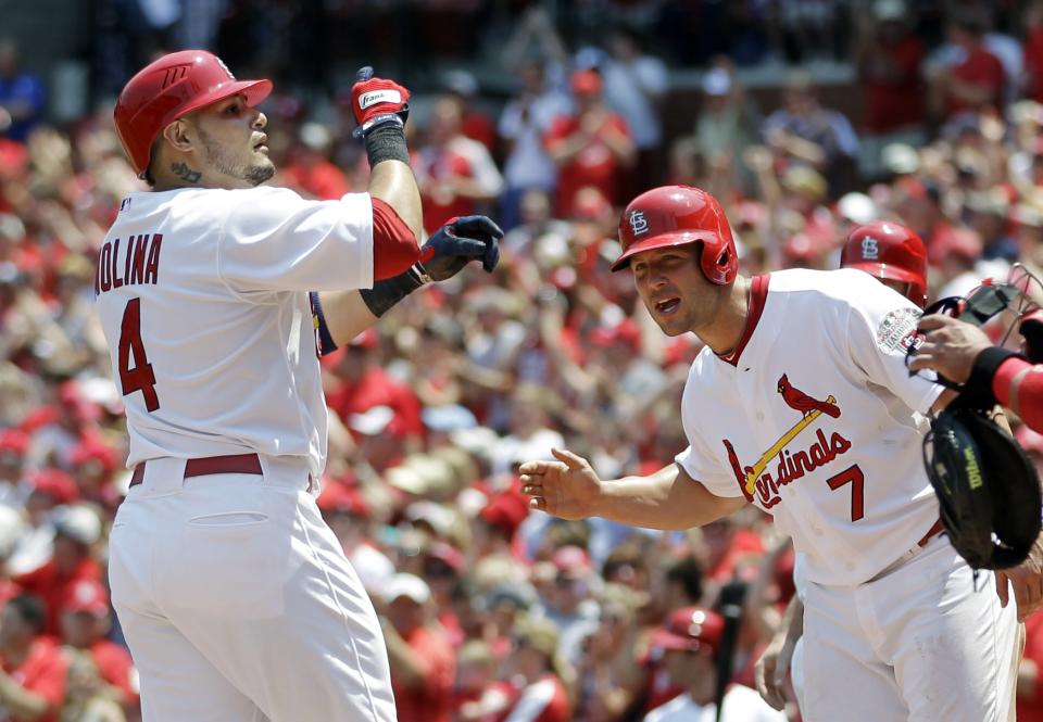St. Louis Cardinals' Yadier Molina, left, celebrates as he reaches home after hitting a grand slam as Matt Holliday, right, waits to greet him during the first inning of a baseball game against the Philadelphia Phillies, Sunday, May 27, 2012, in St. Louis. (AP Photo/Jeff Roberson)