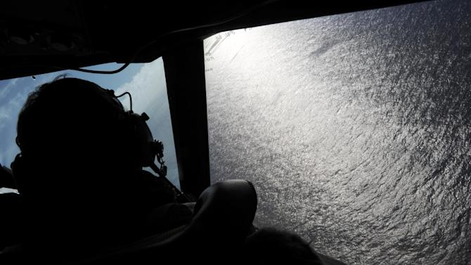 FILE - In this April 13, 2014 file photo, taken from the Royal New Zealand Air Force (RNZAF) P-3K2-Orion aircraft, co-pilot Squadron Leader Brett McKenzie looks out of a window while searching for debris from missing Malaysia Airlines Flight 370, over the Indian Ocean off the coast of western Australia. The yearlong search for Malaysia Airlines Flight 370 has turned up no sign of the plane, but that doesn't mean it's been unproductive. It has yielded lessons and discoveries that could benefit millions, including coastal Australians, air and sea travelers and scientists trying to understand ancient changes to the earth's crust. (AP Photo/Greg Wood, Pool, File)
