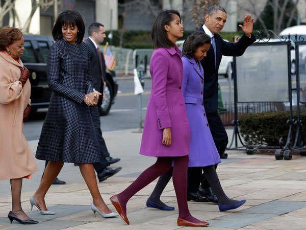 Not to be outdone by their stylish mother, Sasha and Malia Obama take a stylish turn in warm-looking coats.  Malia wears a magenta J. Crew coat while Sasha wears a light purple Kate Spade coat. The bu