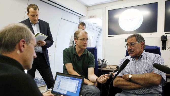 U.S. Secretary of Defense Leon Panetta, right, speaks to the media aboard his aircraft on way to an official visit to Japan, China and New Zealand, Saturday, Sept. 15, 2012. (AP Photo/Larry Downing, Pool)