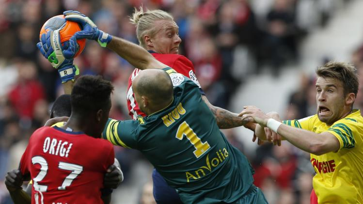 Lille's Kjaer fights for the ball with Nantes' goalkeeper Riou during their French Ligue 1 soccer match in Villeneuve d'Ascq