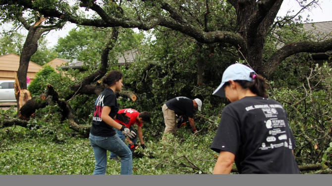 From left, the Keith family, Jordan, Alex, Josh and Connie clean a lot damaged by Wednesday's tornado in Cleburne, Texas on Thursday, May 16, 2013. Ten tornadoes touched down in several small communities in Texas overnight, leaving at least six people dead, dozens injured and hundreds homeless. Emergency responders were still searching for missing people Thursday afternoon. (AP Photo/Ron Russek II)
