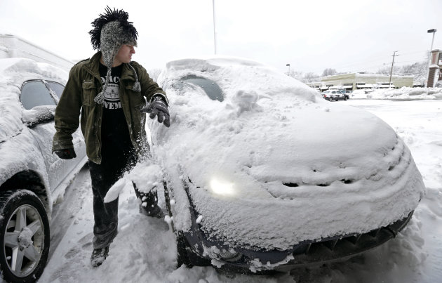 Noah Nichols, of Des Moines, Iowa, cleans snow off his car, Thursday, Dec. 20, 2012, in Des Moines, Iowa. The first widespread snowstorm of the season began a slow crawl across the Midwest on Thursday