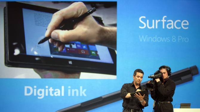 "Mike Angiulo, Corporate Vice President, Windows Planning, Hardware & PC Ecosystem for Microsoft, left, demonstrates the Digital Ink feature of ""Surface"", a new tablet computer running Windows 8 Pro at Hollywood's Milk Studios in Los Angeles Monday, June 18, 2012. The 9.3 millimeter thick tablet comes with a kickstand to hold it upright and keyboard that is part of the device's cover. It weighs under 1.5 pounds. (AP Photo/Damian Dovarganes)"