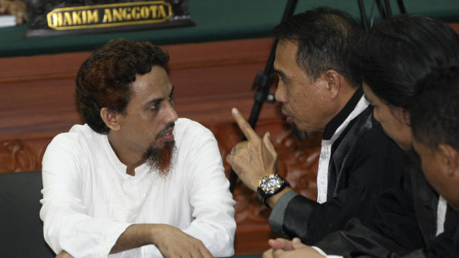Indonesian militant Umar Patek, left, consults with his lawyer Ashludin Hatjani after being sentenced to 20 years in prison at West Jakarta district court in Jakarta, Indonesia, Thursday, June 21, 2012. Patek was convicted guilty of his role in the 2002 Bali bombings that killed 202 people. (AP Photo/Dita Alangkara)