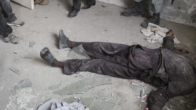 The body of a militant lies on the ground after a gun battle in Kabul, Afghanistan, Monday, April 16, 2012. A brazen, 18-hour Taliban attack on the Afghan capital ended early Monday when insurgents who had holed up overnight in two buildings were overcome by heavy gunfire from Afghan-led forces and pre-dawn air assaults from U.S.-led coalition helicopters. (AP Photo/Musadeq Sadeq)