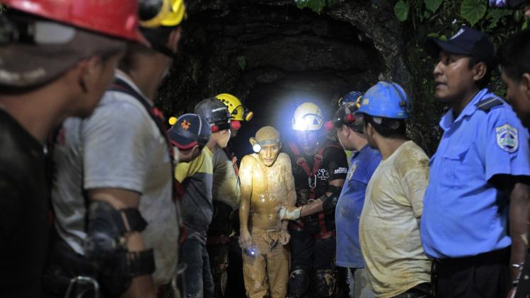Miners and rescue workers hold a miner covered in mud after he was rescued from a gold mine blocked by a landslide in Bonanzas town