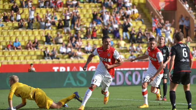 Guingamp's goalkeeper Lossl lunges while AS Monaco's Dirar celebrates with team mates after he scored on goal during their French Ligue 1 soccer match against Guingamp at Louis II Stadium in Monaco