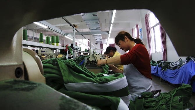 In this Monday, May 20, 2013 photo, workers sew fabrics at a garment factory in Jiujiang in central China's Jiangxi province. China's manufacturing weakened again in June amid a credit crunch and slower U.S. and European orders, two surveys showed Monday, July 1, adding to signs that growth in the world's second-largest economy is decelerating. (AP Photo) CHINA OUT