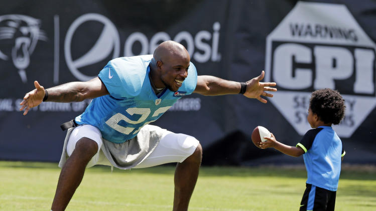 10ThingstoSeeSports - Carolina Panthers' Josh Thomas, left, reaches out to hug his son, Dallas, 2, after an NFL football practice at a training camp in Spartanburg, S.C., Tuesday, July 29, 2014