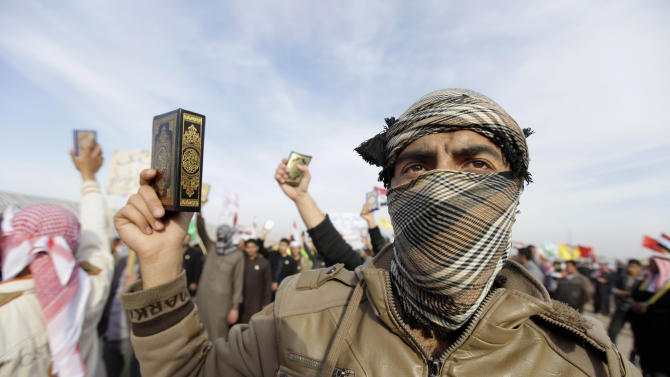 In this Thursday, Jan. 24, 2013 photo, masked men hold copies of the Quran during a protest against Iraq's Shiite-led government in Ramadi, 70 miles (115 kilometers) west of Baghdad, Iraq.  Iraqi insurgents are trying to capitalize on the rage of anti-government protesters and the instability caused by rising civil unrest, complicating the government's efforts to stamp out a resurgent al-Qaida and other extremists. (AP Photo/ Khalid Mohammed)