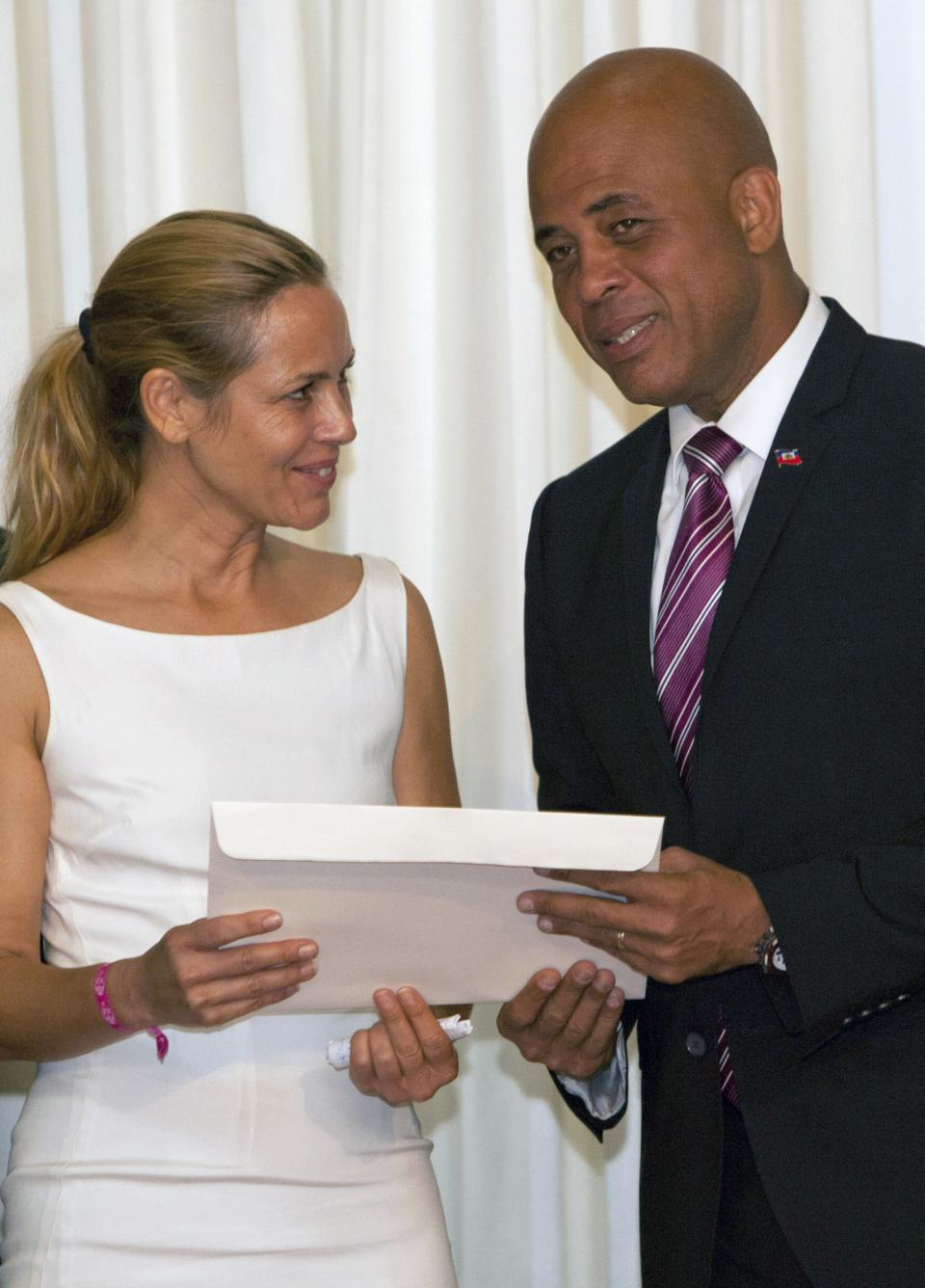 Haiti's President Michel Martelly, right, gives a certificate to actress Maria Bello during a ceremony honoring new goodwill ambassadors at the National Palace in Port-au-Prince, Haiti, Tuesday, Oct. 23,  2012. Bello is the co-founder of women's grassroots group We Advance. (AP Photo/Dieu Nalio Chery)