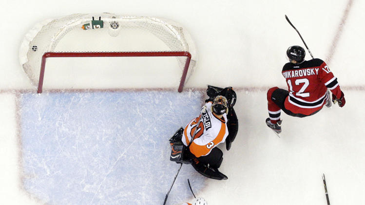 New Jersey Devils' Alexei Ponikarovsky (12), of Ukraine, scores against Philadelphia Flyers goalie Ilya Bryzgalov, center, of Russia, and Flyers' Andreas Lilja, of Sweden, during overtime in Game 3 of a second-round NHL hockey Stanley Cup playoff series, Thursday, May 3, 2012, in Newark, N.J. The Devils won 4-3 and took a 2-1 lead in the series. (AP Photo/Julio Cortez)