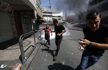 Protesters run from gas fired by Palestinian riot police trying to stop protesters from clashing with Israeli troops, during a protest against Israeli offensive in Gaza, in West Bank city of Hebron