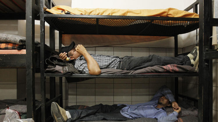 Antonio Perez, bottom, joins dozens of immigrants, many of them Mexican citizens, as they relax in sleeping quarters at a well known immigrant shelter, as many are making tough decisions on whether to try their luck at trying to make it to the United States, by illegally crossing the border, Thursday, Aug. 9, 2012, in Nogales, Mexico.  The U.S. government has halted flights home for Mexicans caught entering the country illegally in the deadly summer heat of Arizona's deserts, a money-saving move that ends a seven-year experiment that cost taxpayers nearly $100 million.(AP Photo/Ross D. Franklin) (AP Photo/Ross D. Franklin)