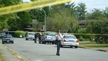 RCMP officers work behind police tape in Richmond, B.C. Tuesday.