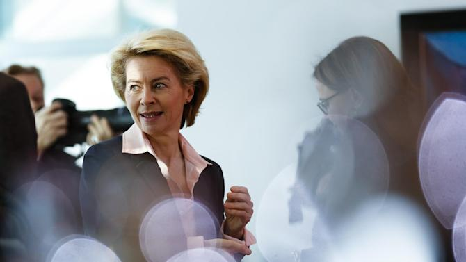 German Defense Minister Ursula von der Leyen arrives for the weekly cabinet meeting at the chancellery in Berlin, Germany, Wednesday, March 4, 2015. Reflections in the picture are from bottles and pots on the desk. (AP Photo/Markus Schreiber)
