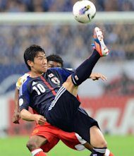 Japan's forward Shinji Kagawa kicks the ball before Oman's forward Raed Ibrahim Saleh during their World Cup 2014 Asia zone Group B football qualification match in Saitama stadium in Saitama on June 3, 2012. AFP PHOTO / TOSHIFUMI KITAMURA