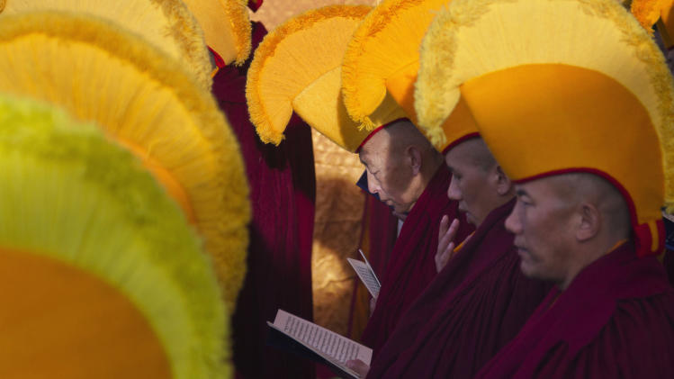 Exiled Tibetan Buddhist monks of the Gelugpa sect in ceremonial yellow hats usher in the Tibetan New Year or Losar with ritual prayers at the Tsuglakhang temple in Dharmsala, India, Monday, Feb. 11, 2013.  (AP Photo/ Ashwini Bhatia)