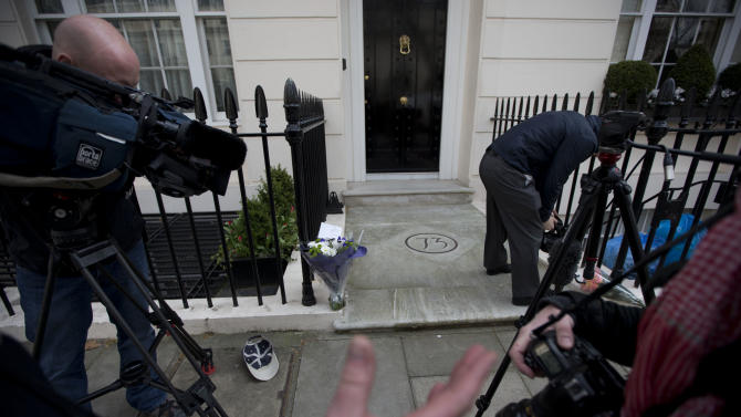 "Members of the media film and photograph floral tributes laid outside the home of the late former British Prime Minister Margaret Thatcher in London, Monday, April 8, 2013.  Margaret Thatcher, the combative ""Iron Lady"" who infuriated European allies, found a fellow believer in Ronald Reagan and transformed her country by a ruthless dedication to free markets in 11 bruising years as prime minister, has died. She was 87 years old.  (AP Photo/Matt Dunham)"