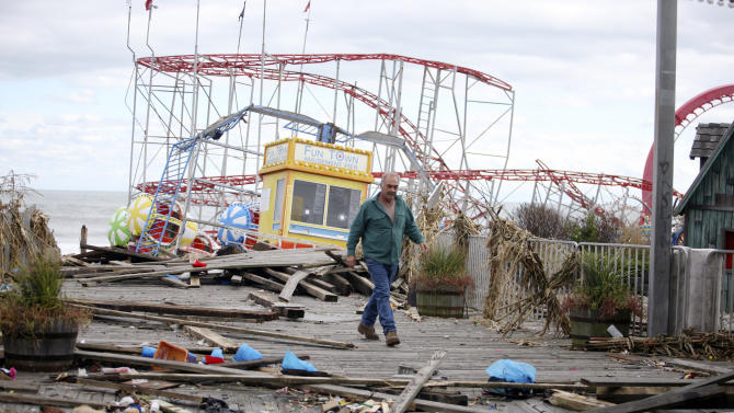 The Fun Town Pier in Seaside Heights has been heavily damaged. Owner Billy Major surveys the damage Wednesday, Oct. 31, 2012. Only four of the rides on the pier survived superstorm Sandy. (AP Photo/Star-Ledger, David Gard/POOL)