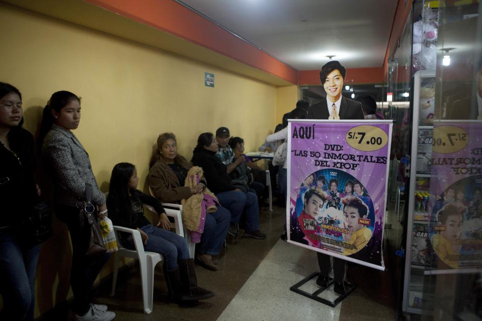 In this May 4, 2013 photo, parents and their children wait for a store to open that sells Korean pop music, known as K-Pop, at the Arenales shopping center in Lima, Peru. Arenales has entire floors dedicated to South Korean music, clothes and food. (AP Photo/Martin Mejia)