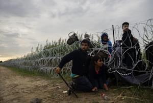 Migrants cross the wire fence at the border between…