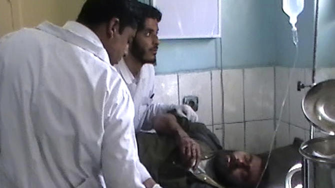 This image made from AP video shows doctors attending to an injured man at the local hospital in Farah, western Afghanistan, Wednesday, April 3, 2013. Suicide bombers disguised as Afghan soldiers stormed a courthouse Wednesday in a failed bid to free more than a dozen Taliban prisoners in western Afghanistan, officials said. Scores of people, including the attackers, were reported killed in the fighting. The assault in Farah province was the latest example of the Taliban's ability to strike official institutions despite tight security measures. (AP Photo/APTN)
